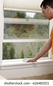 Mature male dusting an interior window sill ledge of a screened and open home bathroom window. Man cleaning dust allergens from a window sill with a cloth rag.