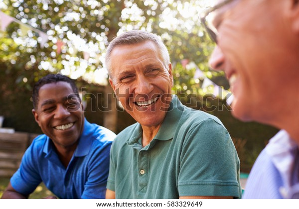 Mature Male Friends Socializing In Backyard Together
