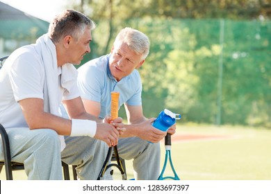 Mature male friends talking while sitting with tennis rackets and water bottle on chair at court