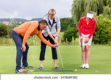 Mature male golf trainer teaching the couple to play golf on golf course