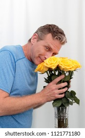 Mature male holds a dozen yellow pink roses happy. Man smilies smelling a bunch of aromatic roses. Middle-aged man holds a yellow pink roses bouquet, thankful for the aroma smiling at the viewer.