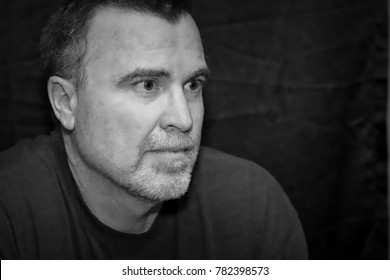 Mature male looks serious in black and white portrait