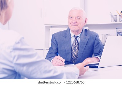 Mature male manager listening attentively to visitor in his office