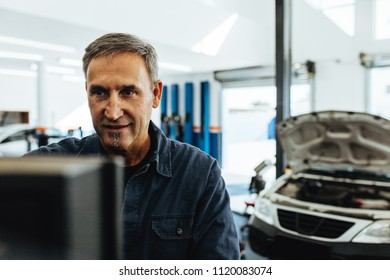 Mature male mechanic checking a car with computer.  Mechanic doing car diagnostic on computer.