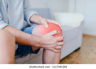 Mature male patient holding knee in pain. Man with knee pain. Man with chronic knee problems and pain Man with his hands on a painful leg. Leg pain