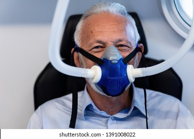 Mature male patient wearing oxygen mask during hyperbaric oxygen therapy and looking at camera.