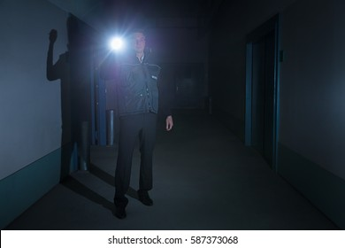 Mature Male Security Guard With Flashlight Standing In Corridor Of The Building