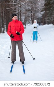 Mature male skier and woman stay on skis in winter snow skiing run