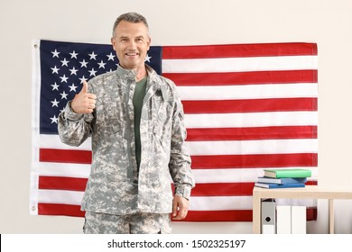 Mature male soldier showing thumb-up near wall with USA flag