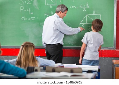 Mature male teacher assisting little schoolboy while solving mathematics on board in classroom