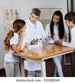 Mature male teacher explaining molecular structures to students at desk in science lab