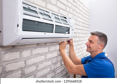 Mature Male Technician Fixing Air Conditioner With Screwdriver