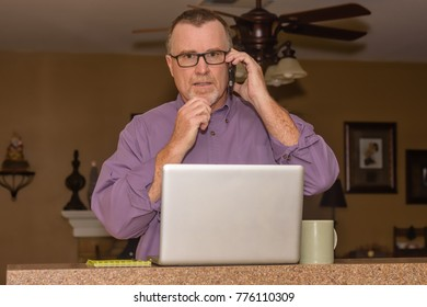 Mature male thinking while on phone during home office day