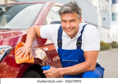 Mature male worker cleaning red car with cloth and spray bottle