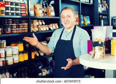 Mature man 56s standing near counter with assortment of grocery products