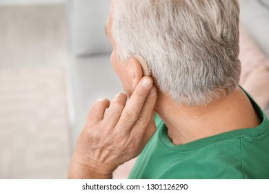 Mature man adjusting hearing aid at home, closeup