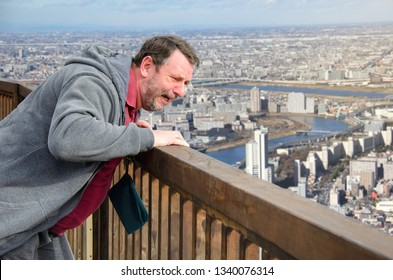 A mature man is afraid of heights. He stands on the observation deck and looks down the panoramic view of big city. This man is very scared. He suffers from acrophobia.