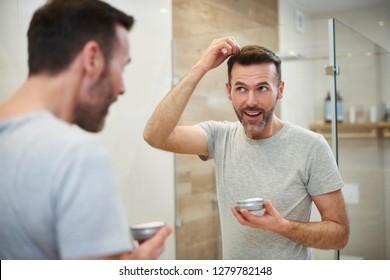 Mature man applying hair gel in the bathroom