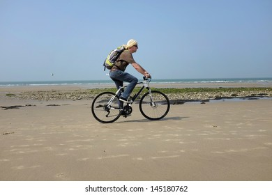 mature man with backpack bicycling on the beach