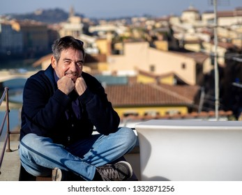 Mature man with a beard, posing seated in front of the ponte vechio in florence, Italy