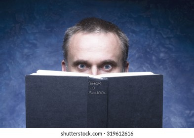 Mature man being focused and hooked by book, reading open book, surprised young man, amazing eyes looking blank cover, back to school written on the spine of the book