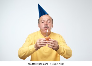 Mature man in birthday cap blowing candle on his cake making a wish. Happy birthday concept