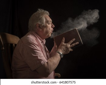 Mature man blowing dust off an old book, taken on a black background