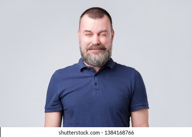 Mature man in blue shirt wrinkled due to sour taste. Grimacing from the unpleasant sensation or sound