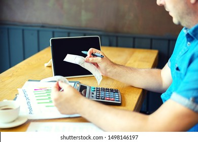 Mature man calculating bills and expenses of small business - Man holding bills paying taxes with internet banking - Caucasian male working with invoice on table