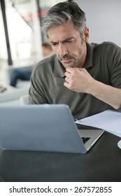 Mature man calculating budget on laptop