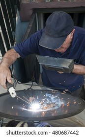 Mature man with cap applying a weld