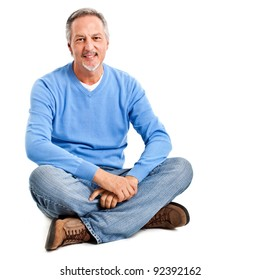Mature man with casual look sitting on the floor isolated on white