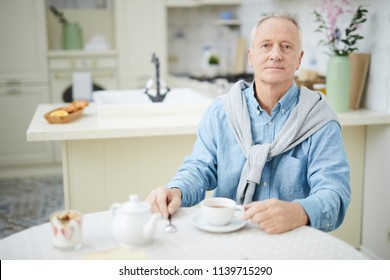 Mature man in casualwear sitting by table in the kitchen and having tea in the morning