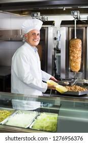 Mature man chef wearing uniform preparing kebab on kitchen in fast-food cafe