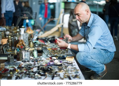Mature man is choosing old things at the antique market outdoor