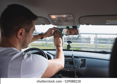 Mature man cleaning rear view mirror in luxury car with a cloth. Selective focus on man's hands.