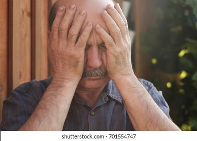 Mature man closing face with hands because of terrible headache or he forgot something