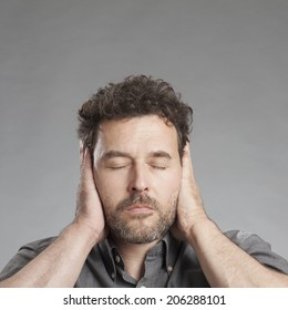 Mature man covering ears with hands