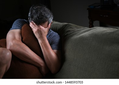 Mature man covering face with hand experiencing high levels of stress and depression