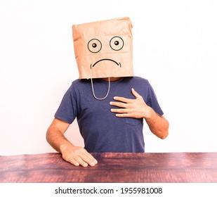 Mature man crestfallen, hiding his identity behind a paper bag over his head.