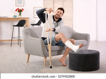 Mature man with crutch and broken leg in cast sitting on sofa at home
