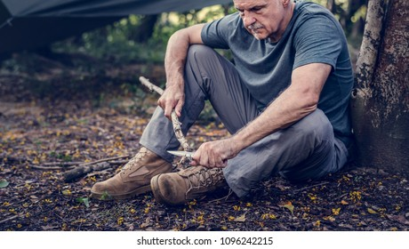 Mature man cutting some firewood
