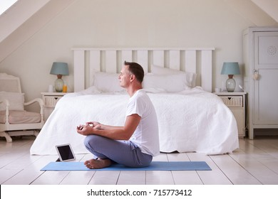 Mature Man With Digital Tablet Using Meditation App In Bedroom