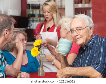 Mature man drinking coffee while friends order at cafe