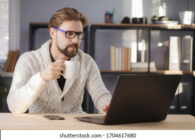 Mature man drinking coffee and working on laptop at home