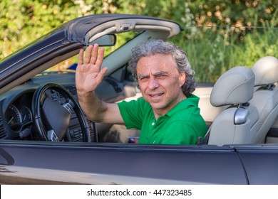 mature man driving a convertible car  is puzzled and he raises his hand to stop or to get attention