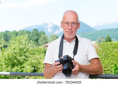 mature man with a dslr camera, outdoors