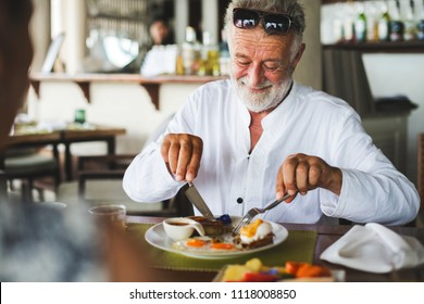 Mature man eating breakfast at hotel