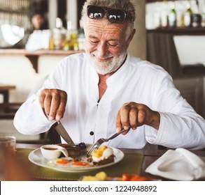 Mature man eating breakfast at hotel