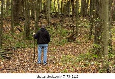 A  mature man is enjoying a hike in the Autumn forest.